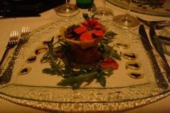 compressé de salmão, tomate confite e rúcula selvagem, acompanhados salada morna de champignons